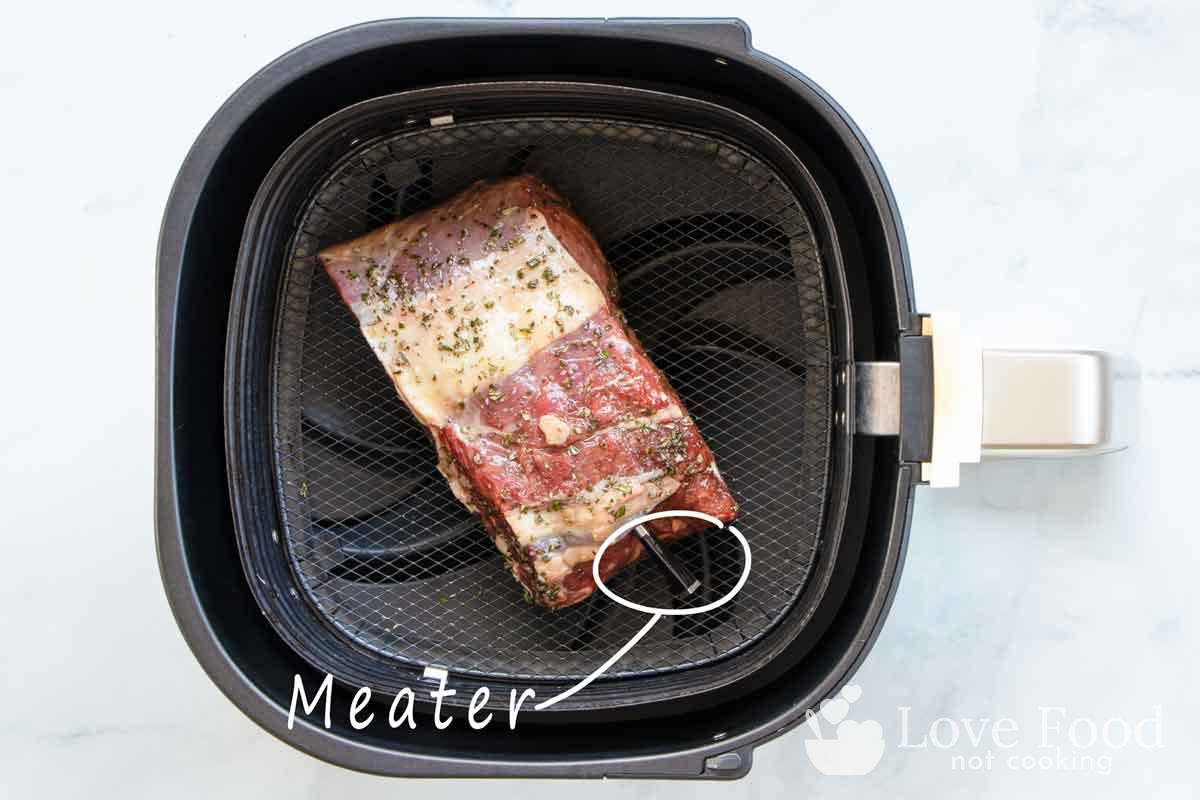 rib eye roast in air fryer basket with Meater meat thermometer.