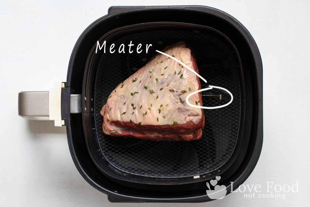 Beef roast in air fryer basket with Meater meat thermometer.