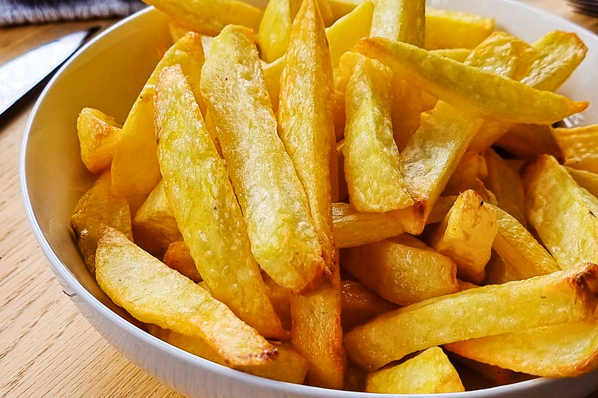 Crispy air fryer homemade french fries in a white bowl.