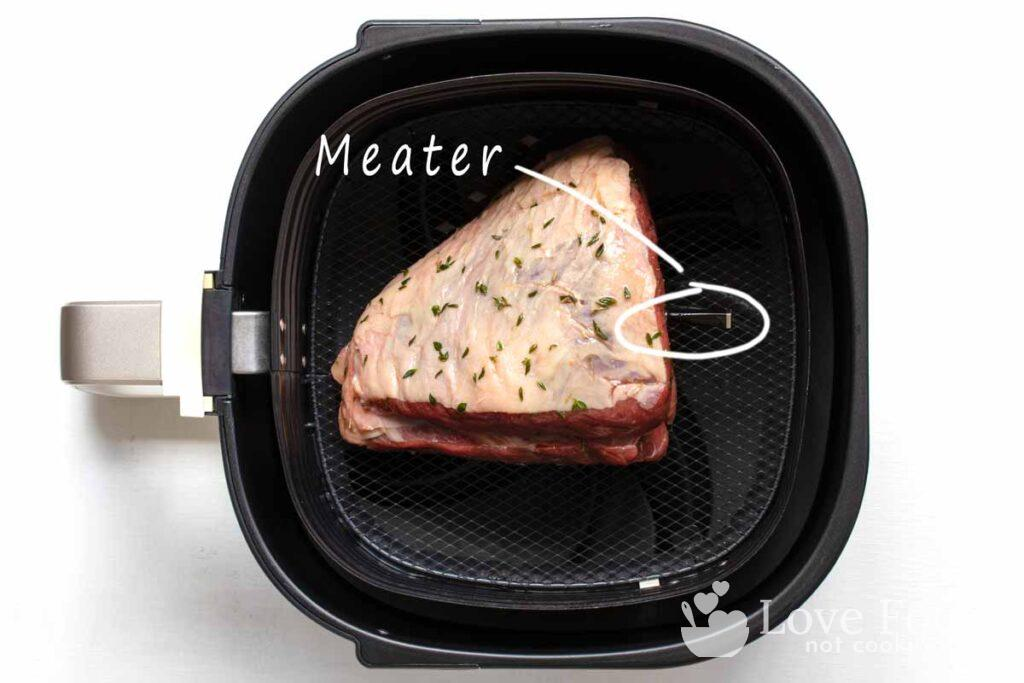 Beef roast in air fryer basket with meat thermometer
