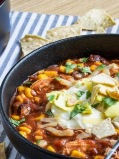 Slow cooker spicy chicken tortilla soup in a black bowl