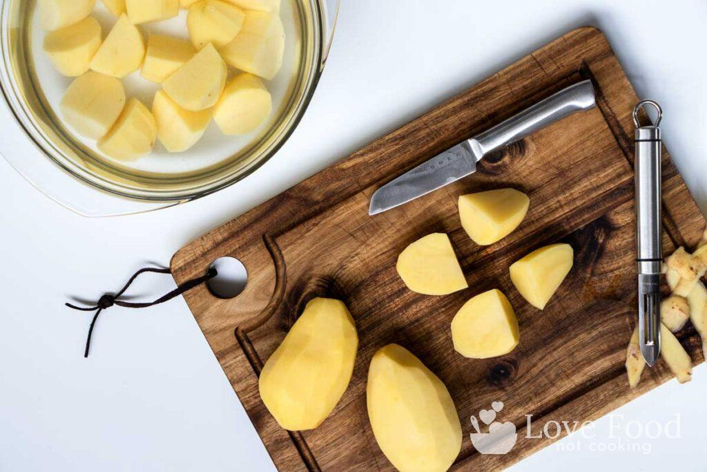 Peeled potatoes being cut on a wooden board.