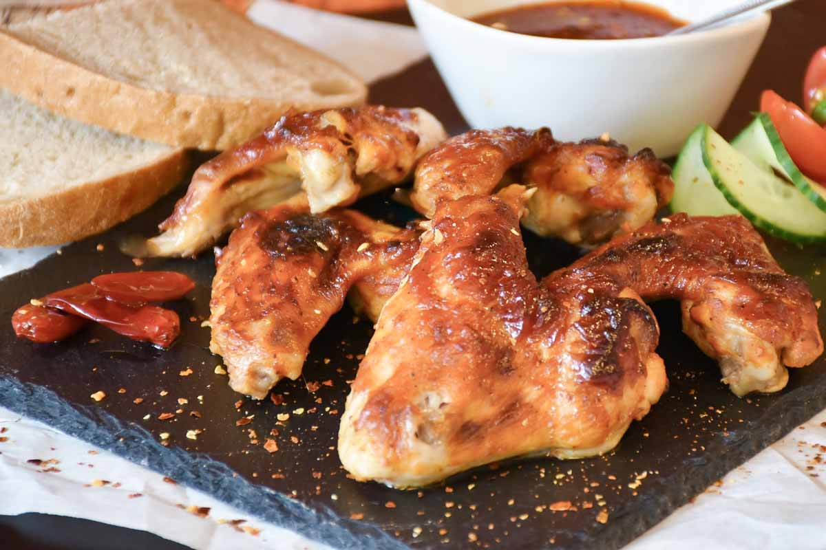 chicken wings with dipping sauce on a black plate.