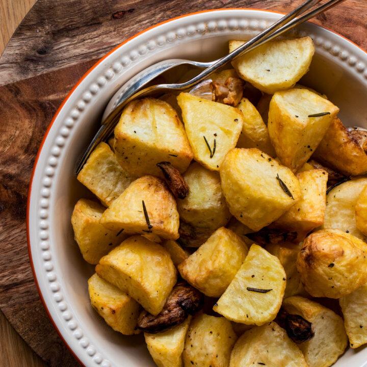 Crispy golden roast potatoes in a dish.