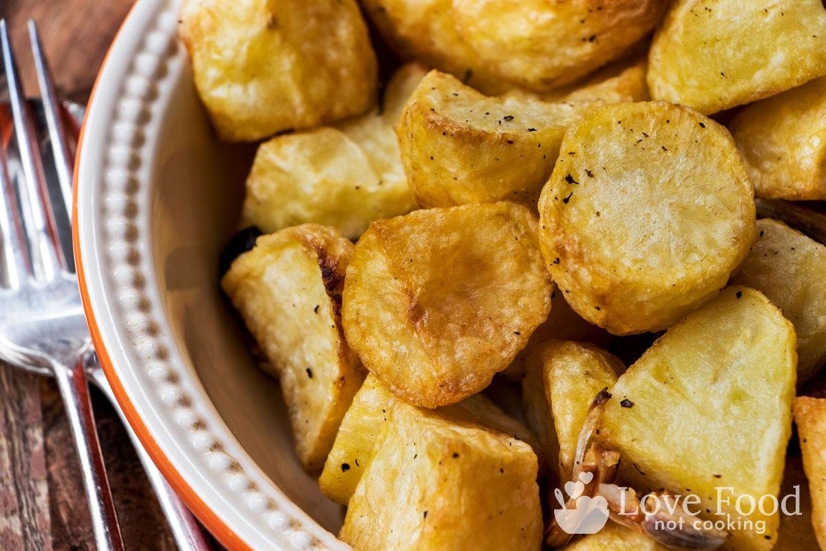 Crispy golden roasted potatoes in a dish.