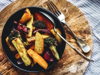 Air fried vegetables in a black bowl.