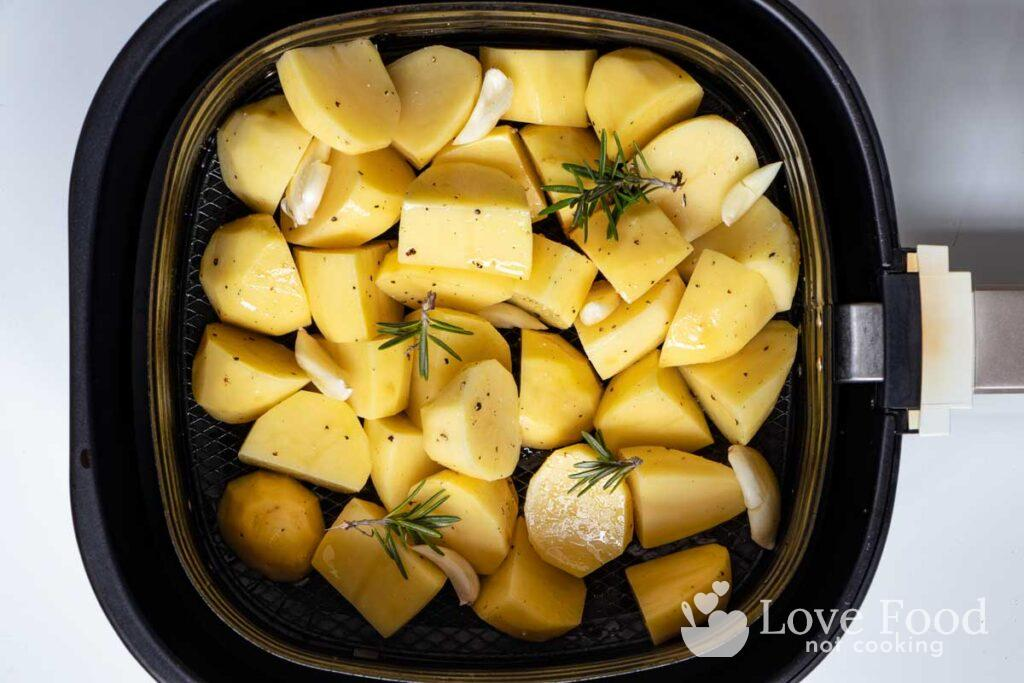 Cut and peeled potatoes in air fryer basket.