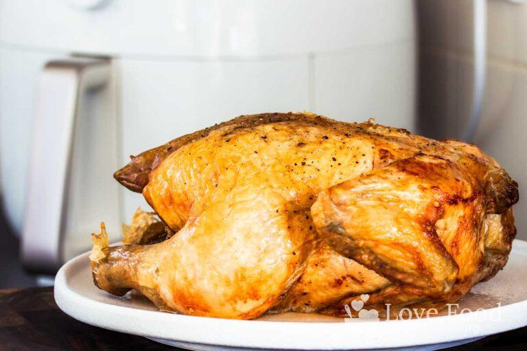 A whole roast chicken in front of air fryer