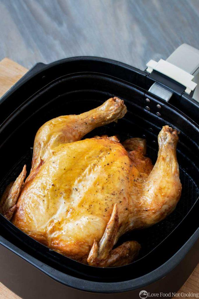 Cooked whole chicken in air fryer basket