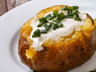 Air fryer baked potato with sour cream and chives on a white plate
