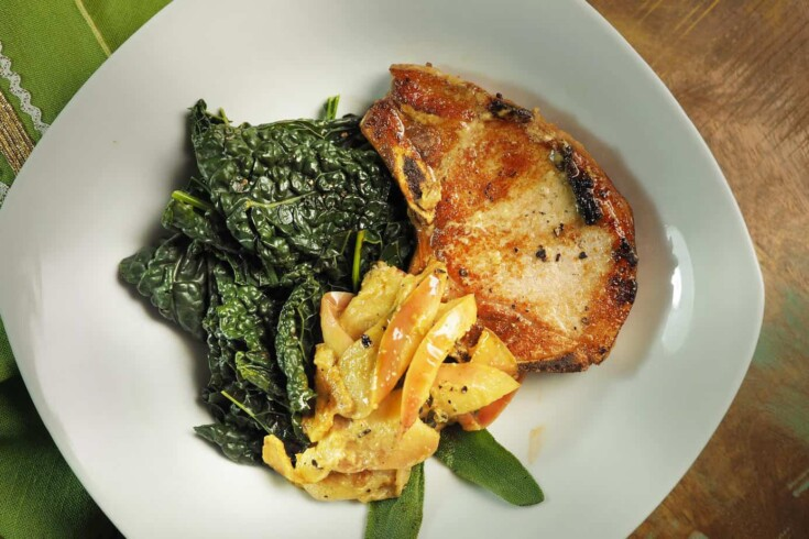 Air Fryer Pork Chops with kale and sliced apple on a white plate