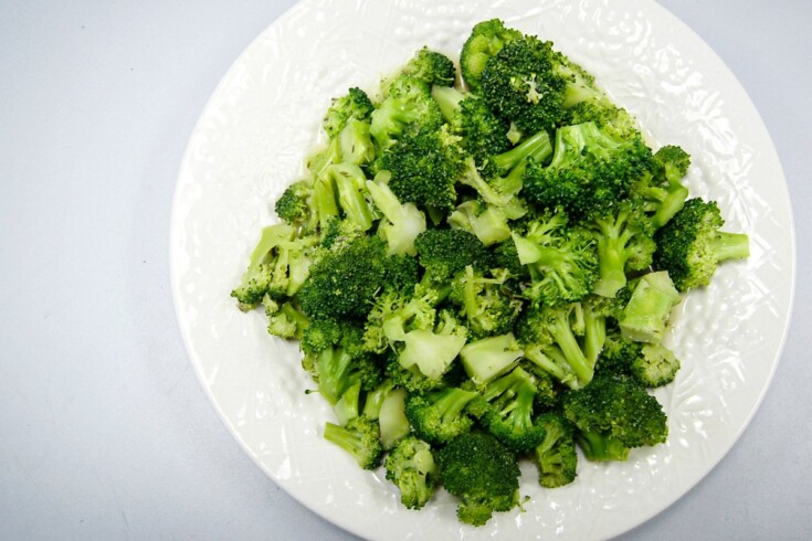Microwave steamed broccoli on a white plate