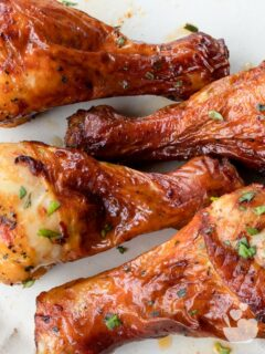 Air fried chicken drumsticks on a cream-colored plate