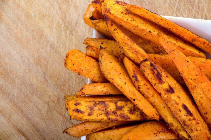 Sweet potato fries on a wooden board.