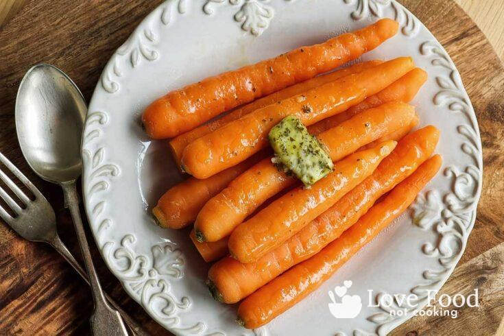 Microwaved carrots on a cream plate with herb butter.