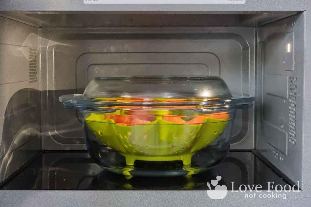 glass bowl containing green microwave steamer basket and carrots in microwave.