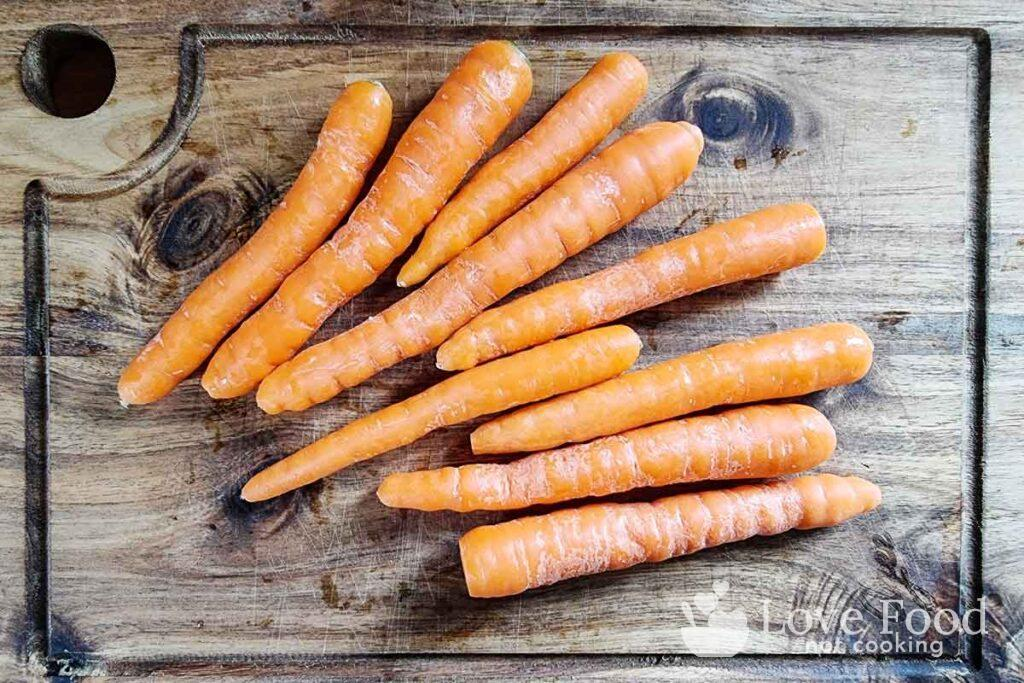 Baby carrots (scrubbed clean) on a wooden board.