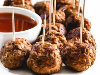 Air fried meatballs with toothpicks in them on a white plate.