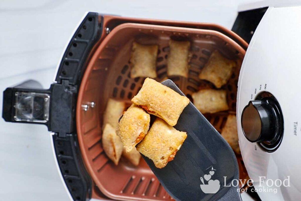 Air fried pizza rolls in air fryer and on a spatula.