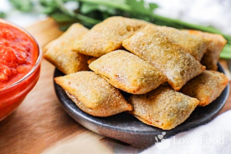 Air fried pizza rolls on a black plate with tomato sauce.