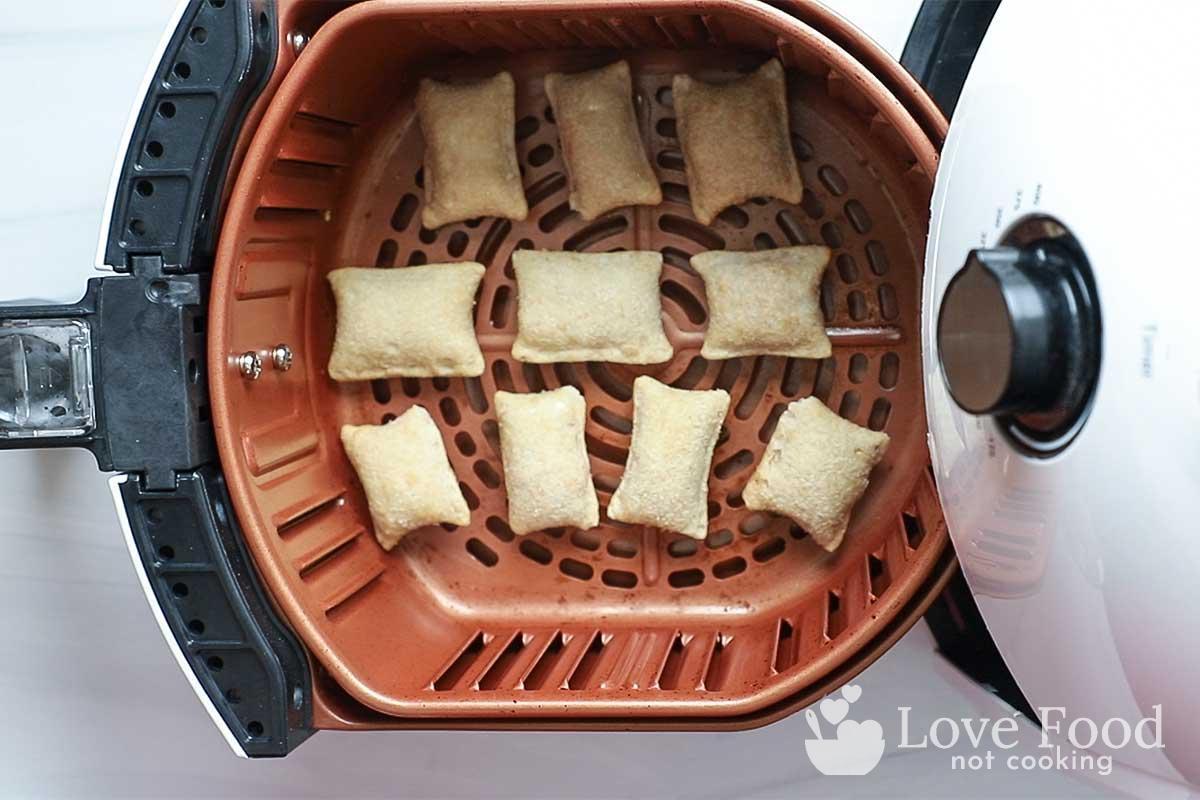 Frozen pizza rolls in air fryer basket.