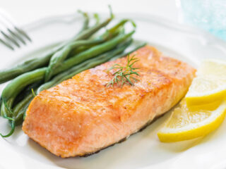 Air fryer salmon with green beans and lemon slices on a white plate.