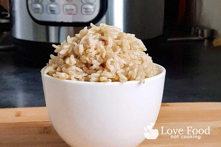 a white bowl of brown rice in front of an Instant Pot.