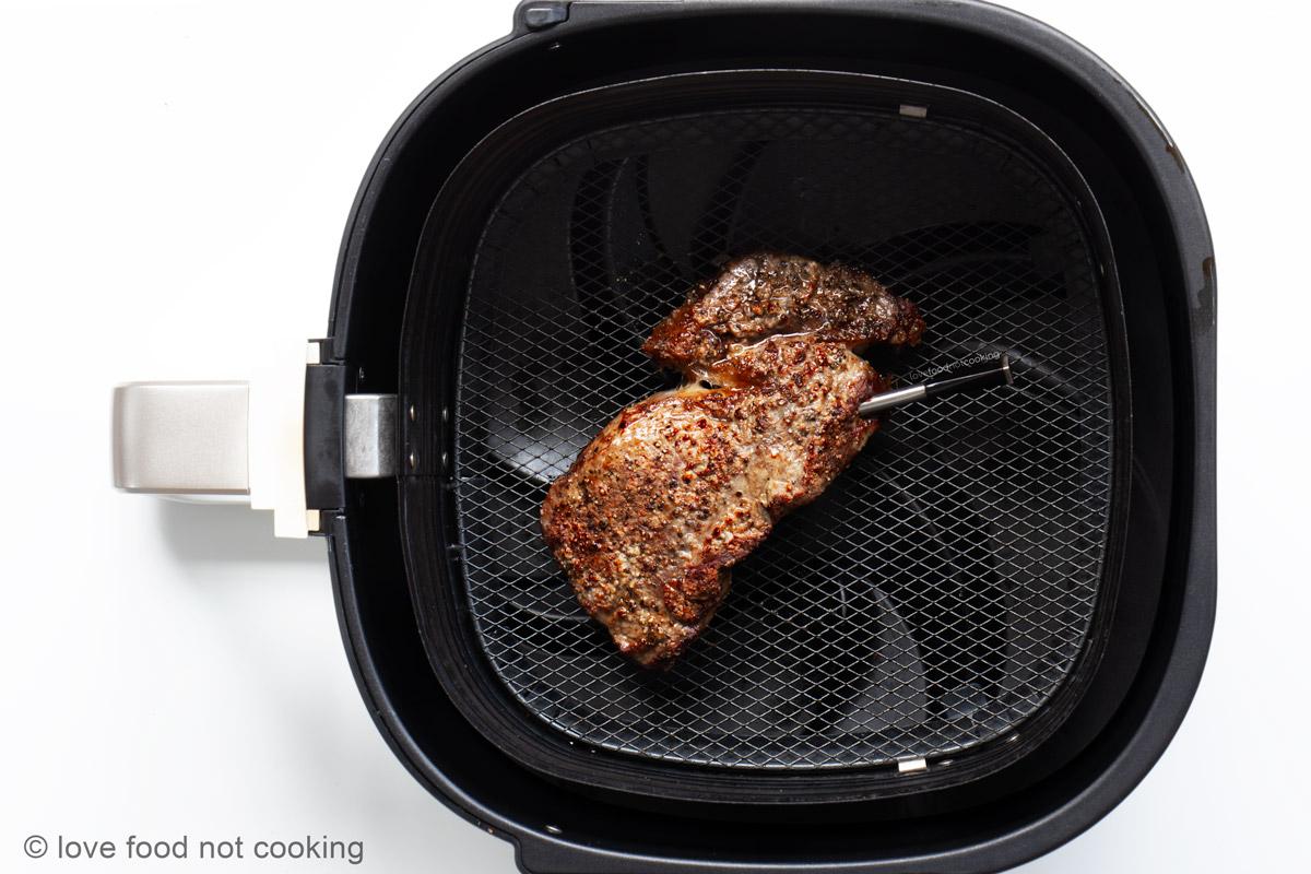 Air fried steak in air fryer basket.