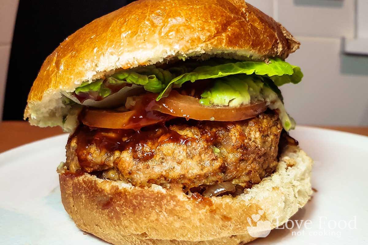 Air fried pork burger with salad and bbq sauce.