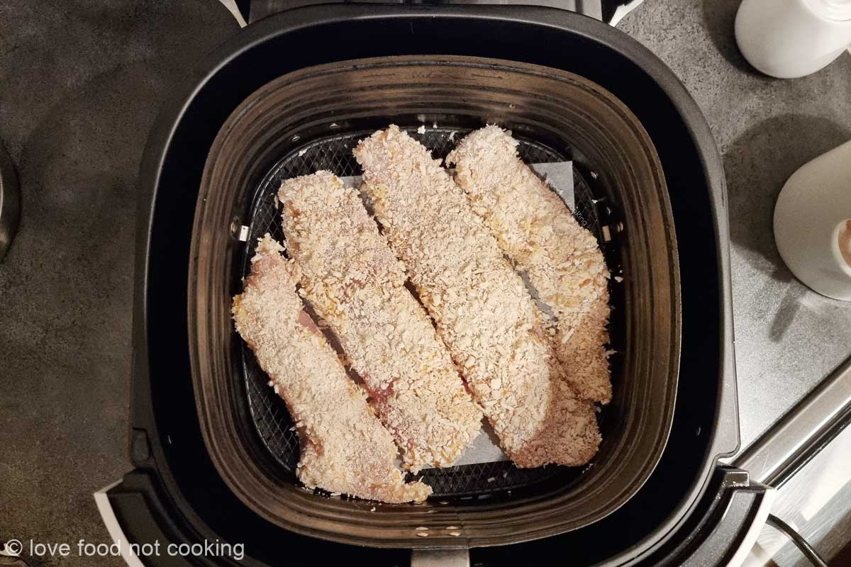 Uncooked tilapia fillets in the air fryer basket.
