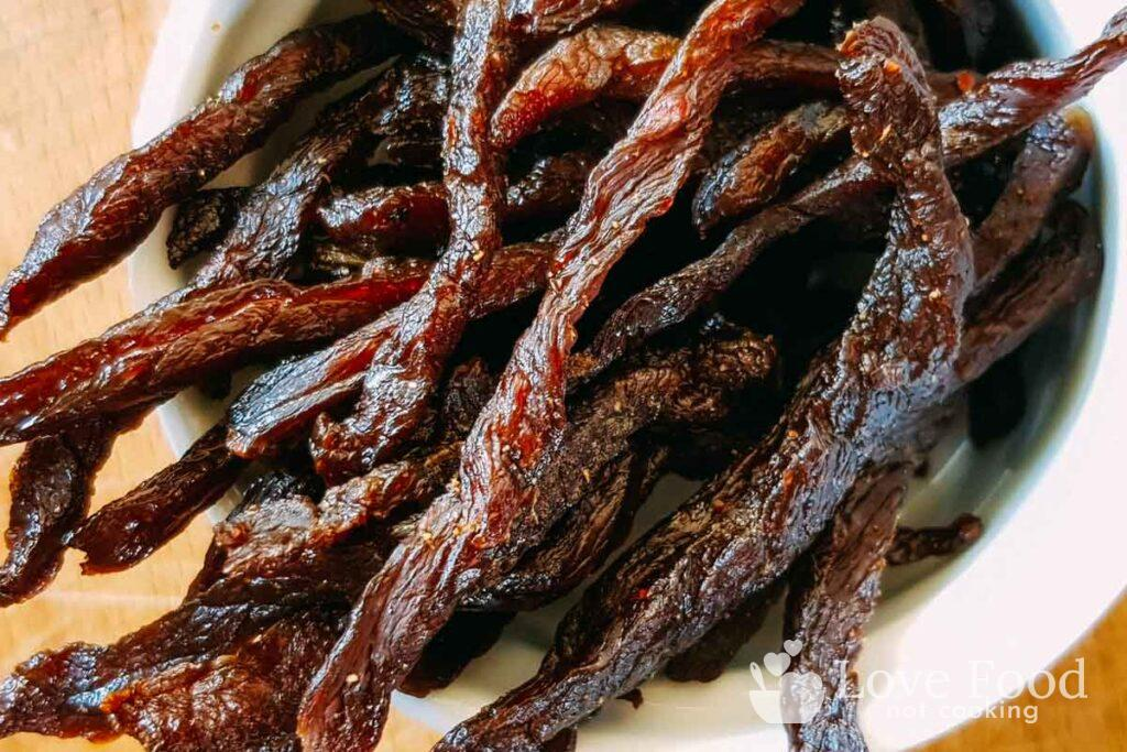 Air fried beef jerky strips in a white bowl.