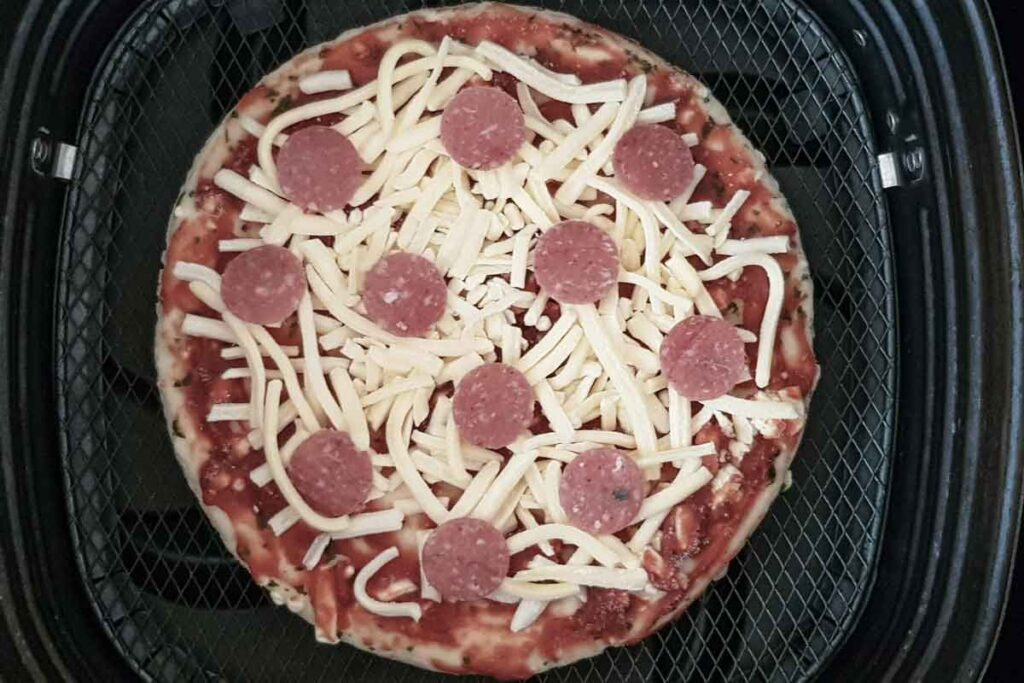Frozen pizza in air fryer basket.