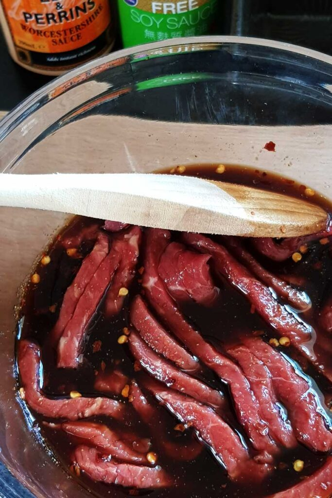 Beef jerky marinating in a glass bowl.