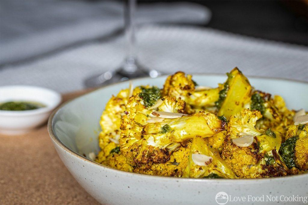 Air Fryer Cauliflower in a grey bowl with flaked almonds and pesto dressing.