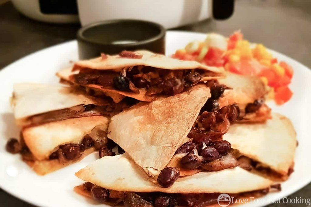 Air fried quesadillas on a white plate with salsa.