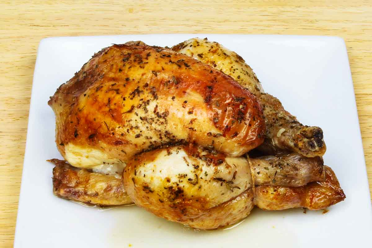 A trussed roaste Cornish hen on a white plate.