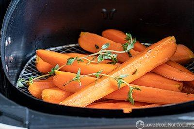 Raw carrots in air fryer basket