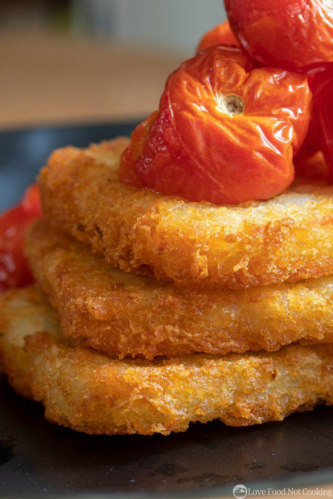 Air fried hash browns on a plate with roasted tomatoes