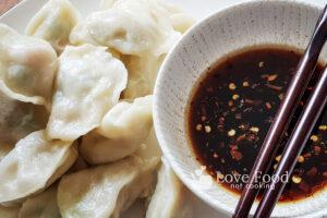Steamed Dumplings om a plate with a bowl of dipping sauce