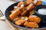 Air Fried Butternut Squash on a black plate with a white dip
