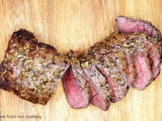 Sliced air fryer beef tenderloin on a wooden board.