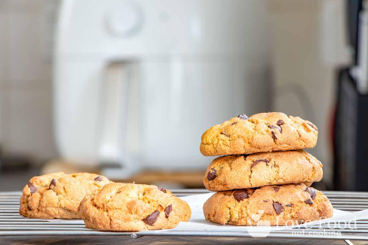 Cookies baked in an air fryer, with an air fryer in the background.