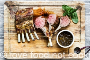 Air fryer rack of lamb on a wooden board with mint leaves and sauce