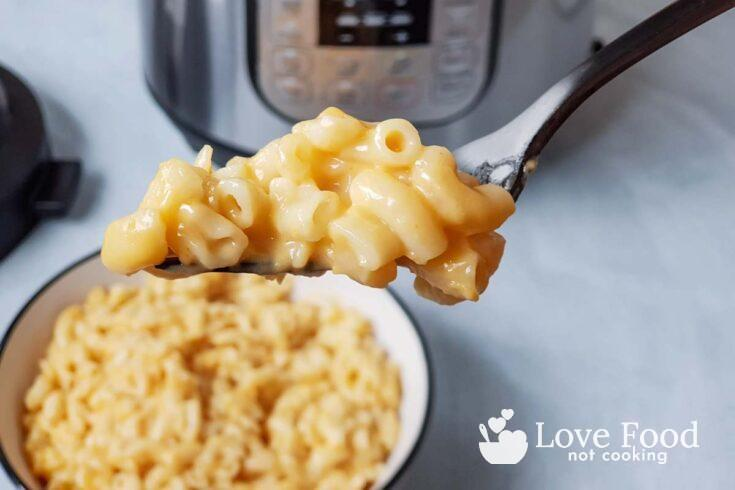 A forkful of mac and cheese in front of an Instant Pot
