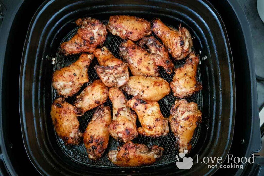 Cooked chicken wings in air fryer basket.