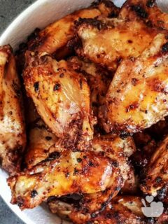 Air fryer lemon pepper chicken wings in a white bowl.