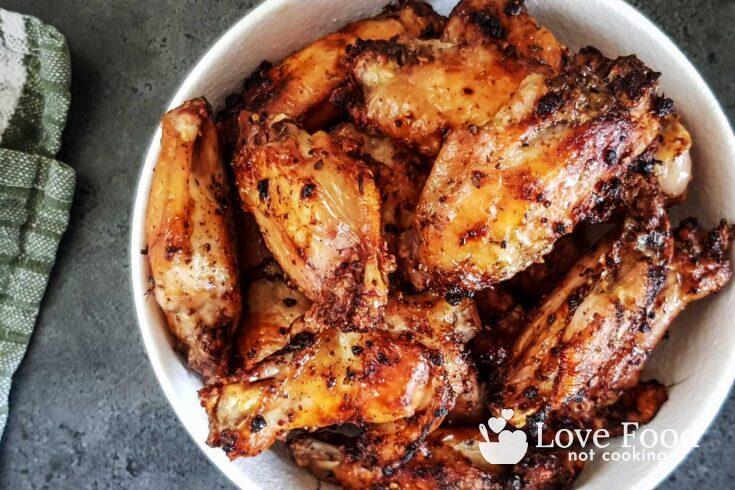 Air fryer lemon pepper chicken wings in a white bowl.