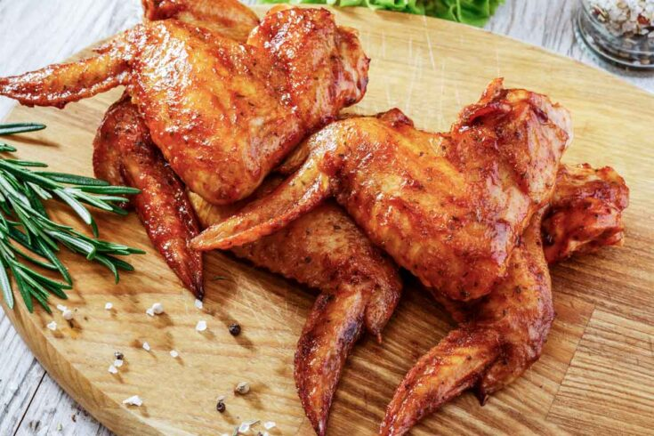 air fried whole chicken wings on a wooden board.