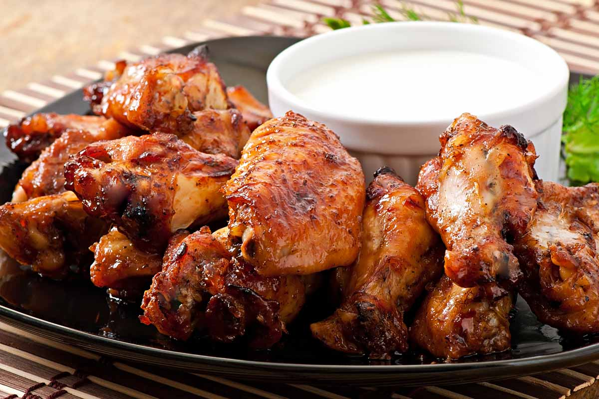 BBQ chicken wings with dipping sauce on a black plate.