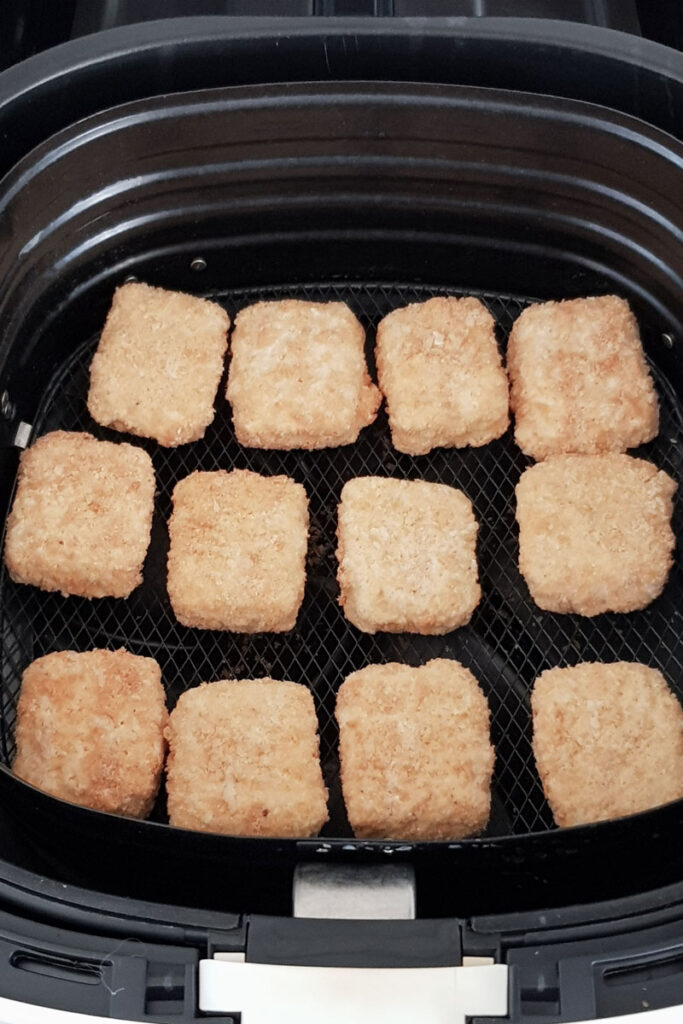 Frozen mac and cheese bites in air fryer basket.
